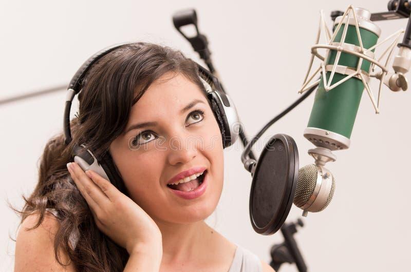 Belle jeune fille chantant dans le studio de musique images stock