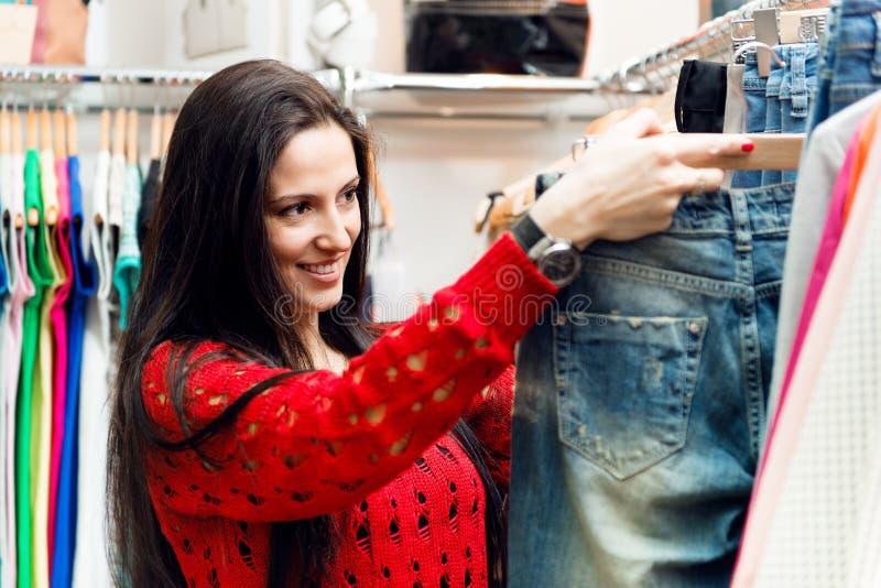 Belle jeune fille choisissant des jeans dans le magasin image libre de droits