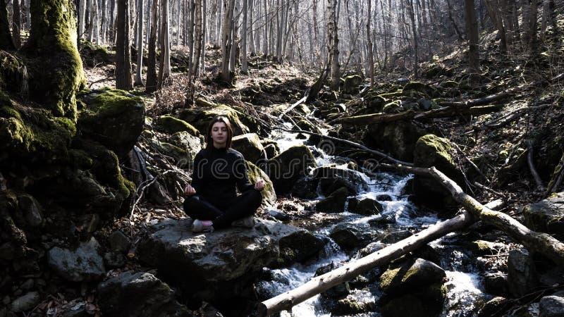 Belle jeune fille concentrée faisant le lotus de pose de yoga se reposant dans une roche sur une rivière méditant dans la forêt a image libre de droits