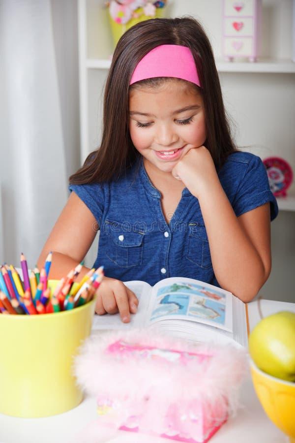 Belle jeune fille d'école lisant un livre images stock