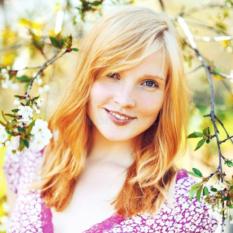 Belle jeune fille dans l'arbre de floraison photographie stock