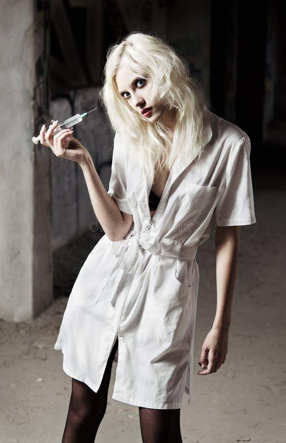 Belle jeune fille dans l'image de l'infirmière folle étrange images stock