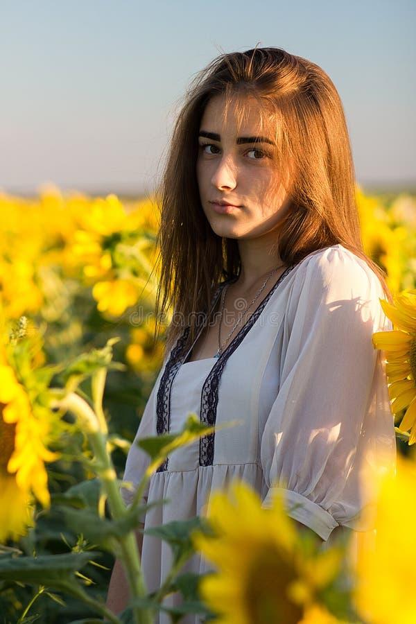 Belle jeune fille dans la robe nationale blanche appréciant la nature photos stock