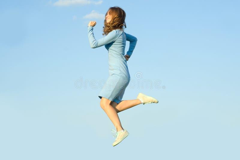 Belle jeune fille dans la robe pulsant dans le saut de ciel photographie stock libre de droits