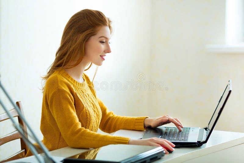 Belle jeune fille dans un chandail jaune et des cheveux rouges image libre de droits