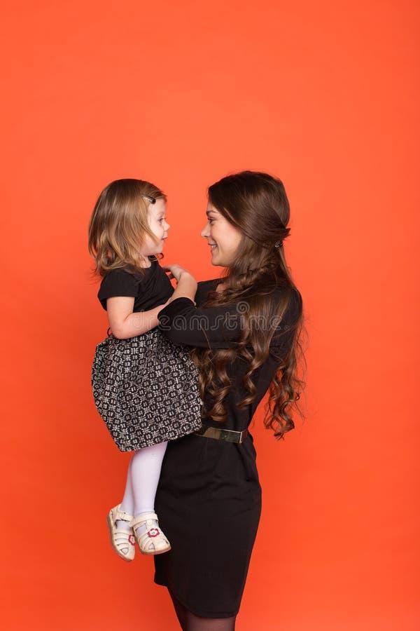 Belle jeune fille dans un costume et petite fille dans un bla photographie stock