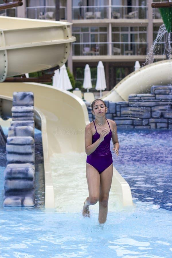Belle jeune fille dans un maillot de bain pourpre sur les waterslides dedans photos libres de droits