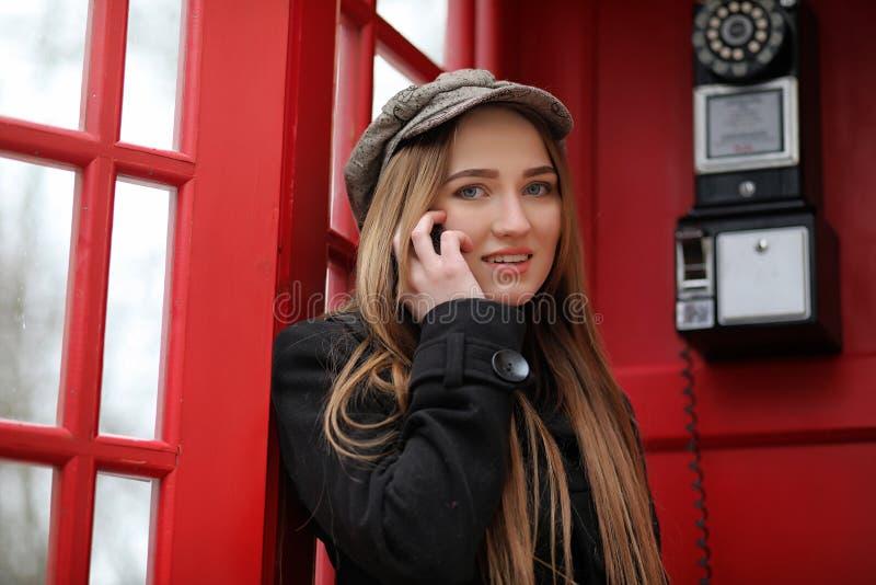 Belle jeune fille dans une cabine de téléphone La fille parle sur le Th photo stock