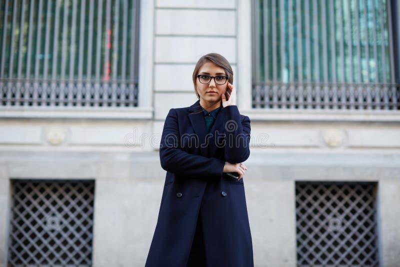 Belle jeune fille de brune avec de longs cheveux se tenant près d'un beau bâtiment photos libres de droits