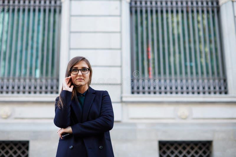 Belle jeune fille de brune avec de longs cheveux se tenant près d'un beau bâtiment images libres de droits