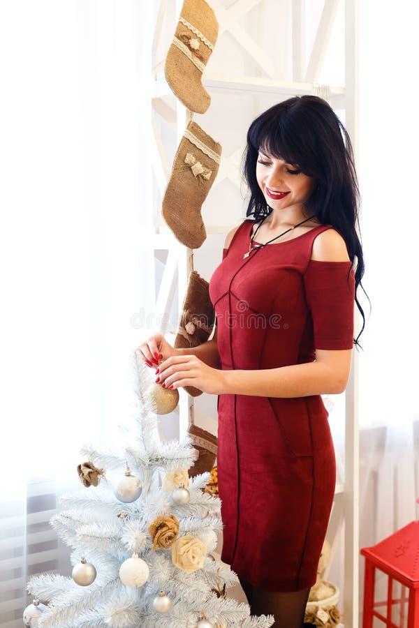 Belle jeune fille de brune dans la robe rouge tenant Noël b photos stock