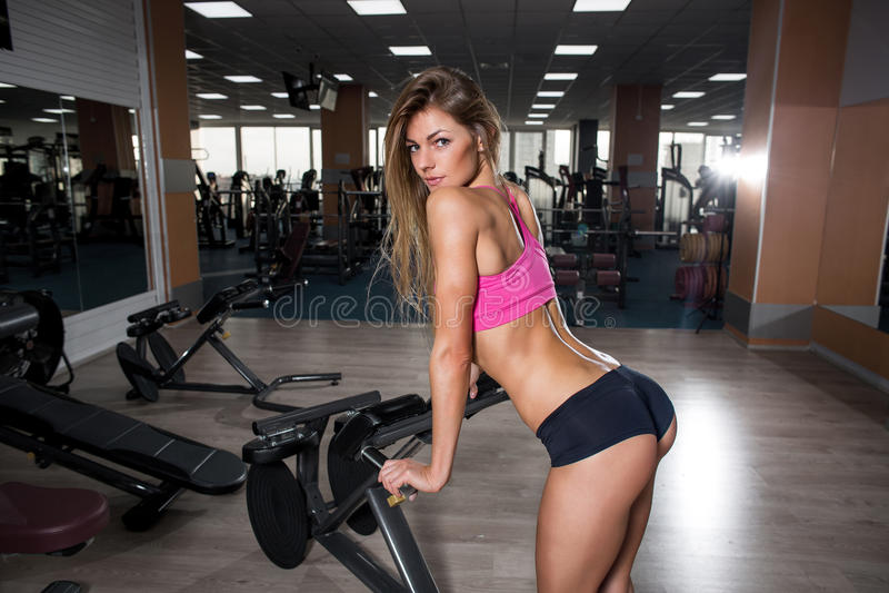 Belle jeune fille de forme physique sexy se reposant après des exercices accroupis photographie stock