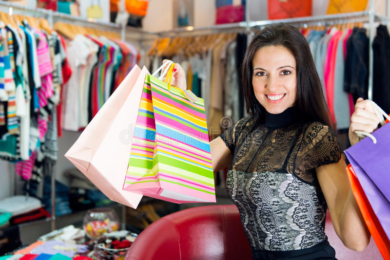 Belle jeune fille de sourire avec des sacs à provisions images stock