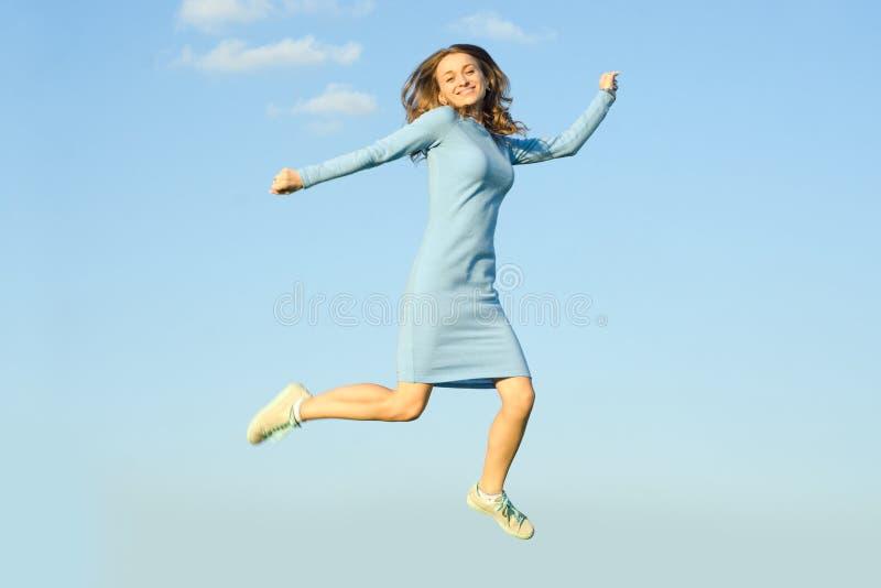 Belle jeune fille en ciel sautant de robe images libres de droits