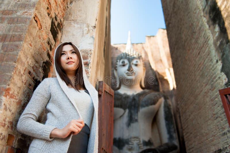 Belle jeune fille et grand Bouddha photographie stock