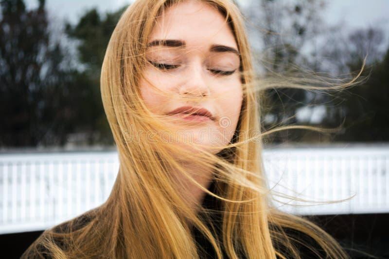 Belle jeune fille Fermez les yeux Cheveu blond vent extérieur Portrait de femme Bonne peau propre Fille heureuse Tir haut étroit  images libres de droits