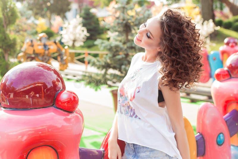 Belle jeune fille gaie avec les cheveux bouclés dans des shorts de denim et le T-shirt blanc à un parc d'attractions au soleil lu photo stock
