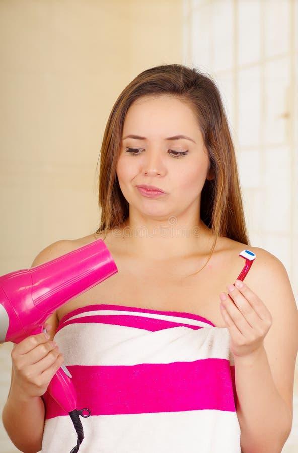 Belle jeune fille hésitante fraîche portant la serviette rose tenant le rasoir séchant ses cheveux photos stock