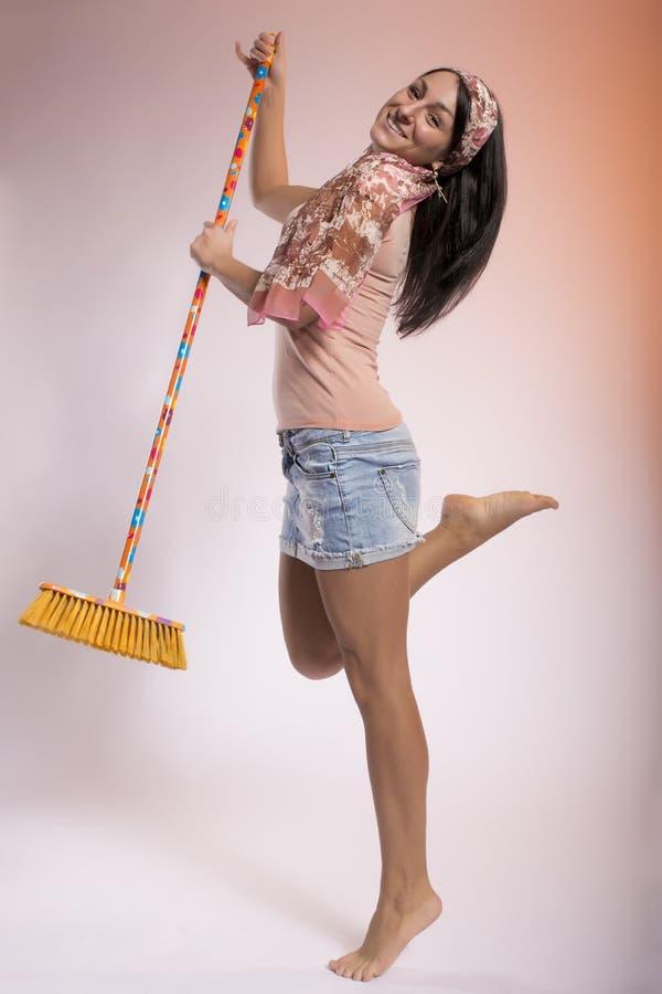 Danse de jeune femme avec un balai image stock