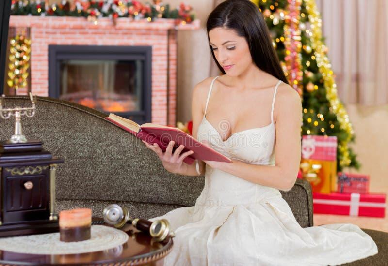 Belle jeune fille lisant un livre la nuit de Noël photos stock