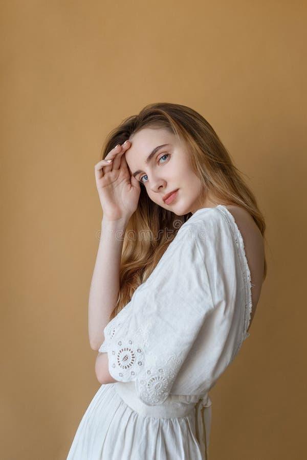 Belle jeune fille maigre avec de longs cheveux dans la robe blanche sur le fond beige avec le sourire mignon regardant la cam?ra photo libre de droits