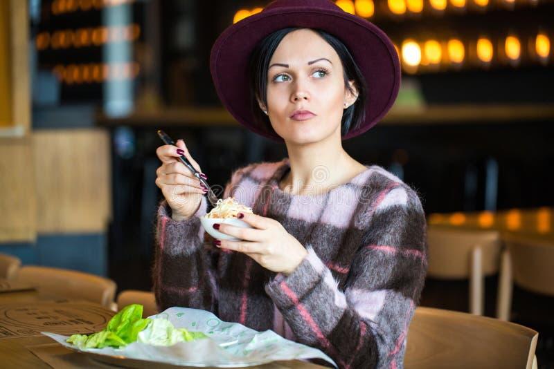 Belle jeune fille mangeant de la salade au café images libres de droits