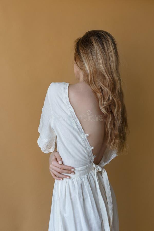 Belle jeune fille mince avec de longs cheveux dans la robe blanche avec le dos nu posant sur le fond beige image libre de droits