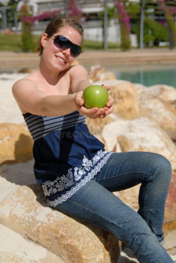 Belle jeune fille offrant la pomme verte photographie stock libre de droits