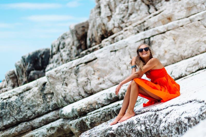 Belle jeune fille par la mer Femme dans une robe rouge sur la plage Vacances de bord de la mer Terrain rocheux photos libres de droits