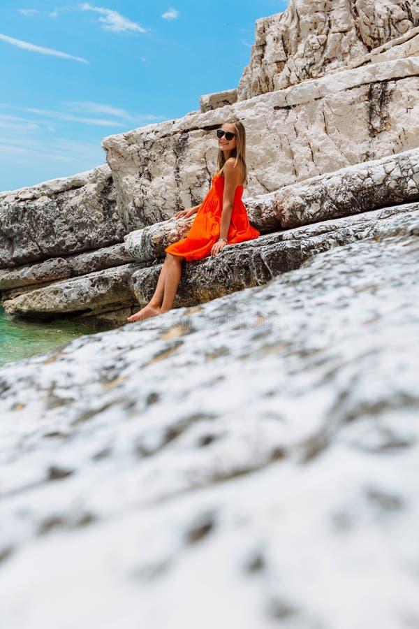 Belle jeune fille par la mer Femme dans une robe rouge sur la plage Vacances de bord de la mer Terrain rocheux photo libre de droits