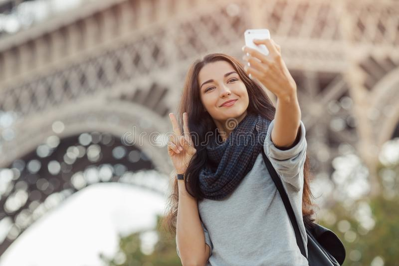 Belle jeune fille prenant le selfie drôle avec son téléphone portable près de Tour Eiffel photos stock
