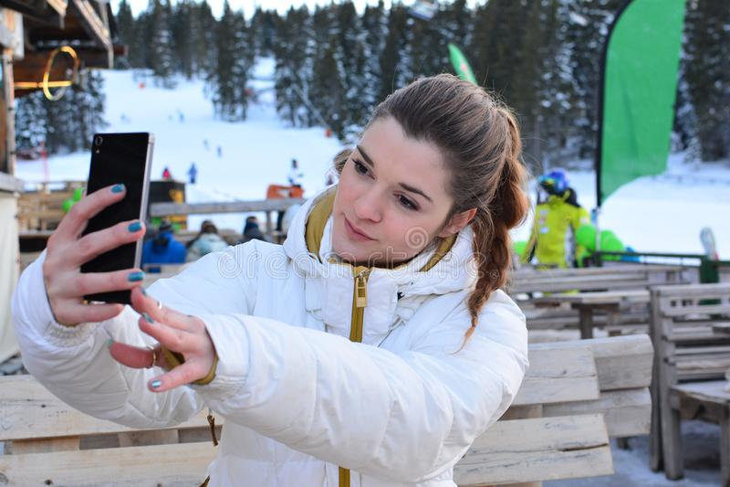 Belle jeune fille qui se selfie après avoir skié photographie stock