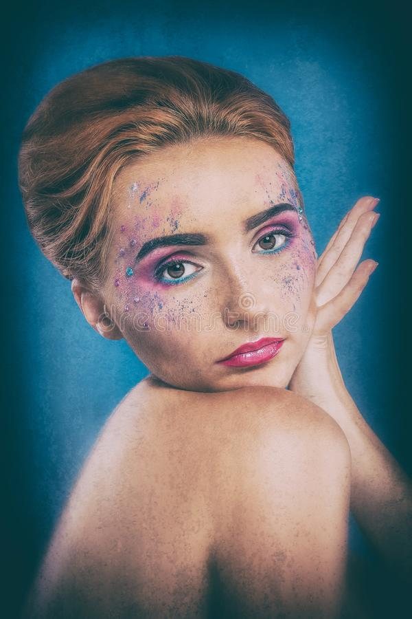 Belle jeune fille rousse avec un pulvérisateur de peinture sur son visage photographie stock