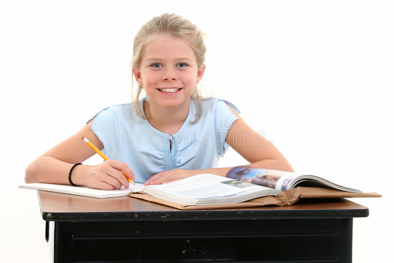 Belle jeune fille s'asseyant au bureau d'école image libre de droits