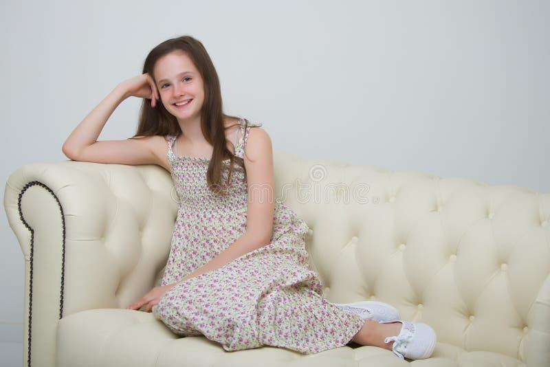 Belle jeune fille s'asseyant sur le sofa par la cheminée images stock
