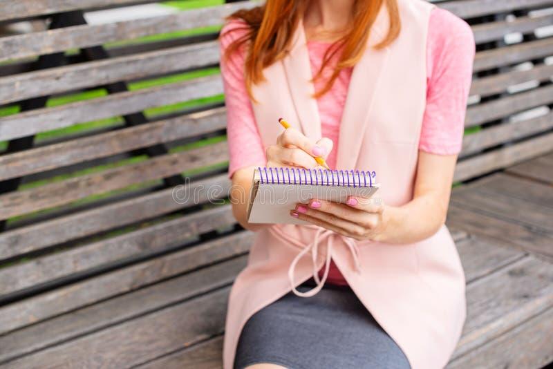 Belle jeune fille s'asseyant sur un banc en bois dans l'écriture ouverte à un foyer sélectif de mode de vie de jour ensoleillé de images stock