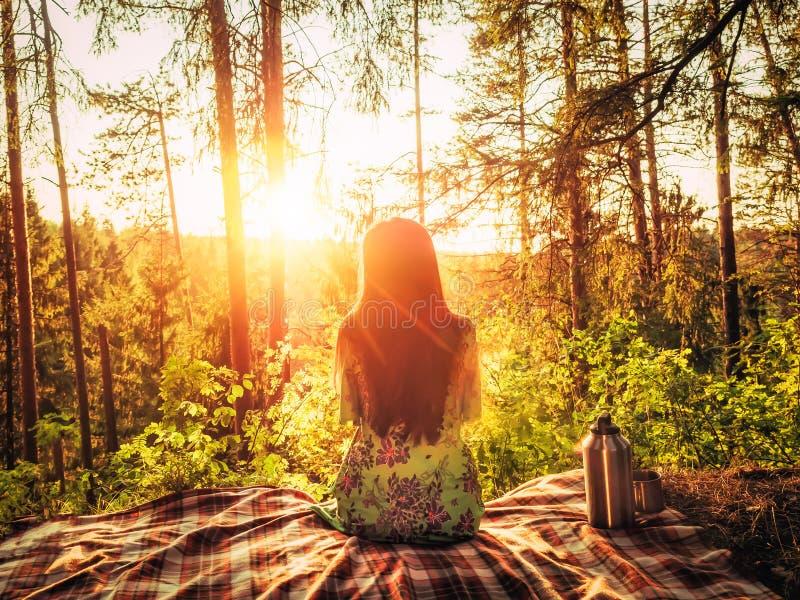Belle jeune fille s'asseyant sur un plaid en clairière de forêt pendant la lumière du soleil lumineuse de coucher du soleil autou images libres de droits