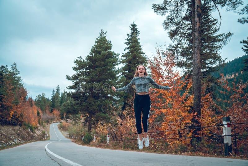 Belle jeune fille sautant pour la joie sur la route dans Svaneti images stock