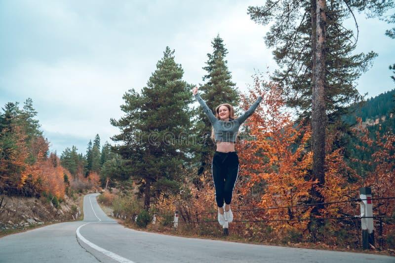 Belle jeune fille sautant pour la joie sur la route dans Svaneti photo libre de droits