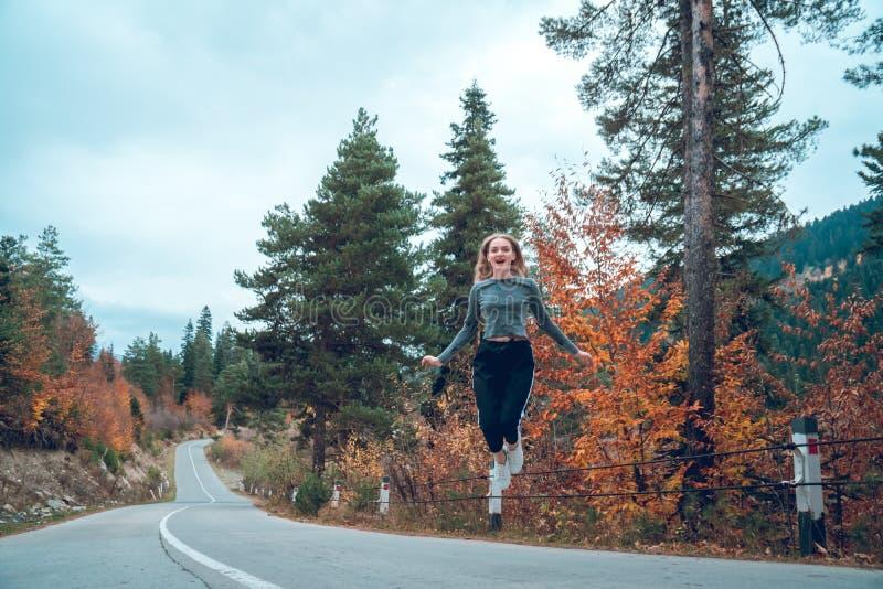 Belle jeune fille sautant pour la joie sur la route dans Svaneti photos libres de droits