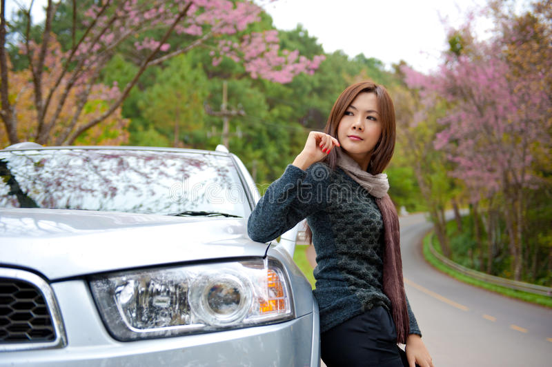 Belle jeune fille se reposant sur le côté de son véhicule images libres de droits