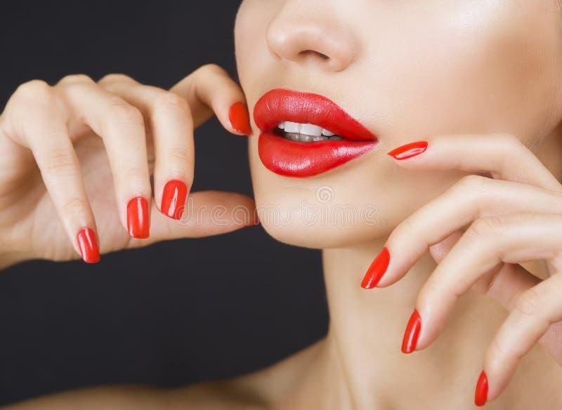 Belle jeune fille sexy avec les lèvres rouges et le vernis à ongles rouge image stock