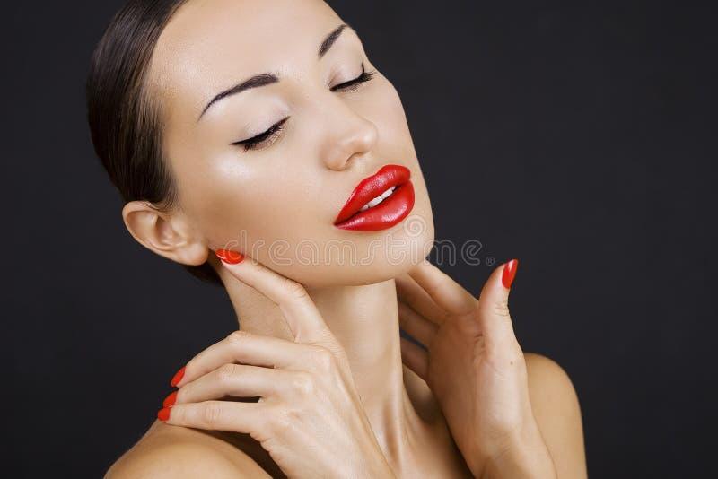 Belle jeune fille sexy avec les lèvres rouges et le vernis à ongles rouge, Bri images libres de droits