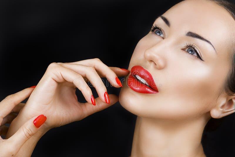 Belle jeune fille sexy avec les lèvres rouges, maquillage lumineux sur l'obscurité image stock