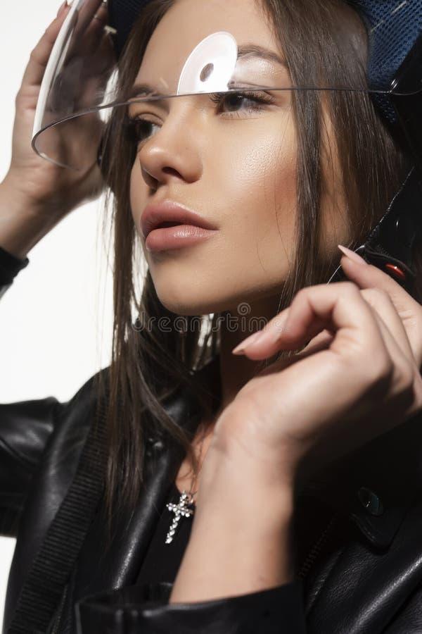 Belle jeune fille sexy de cycliste, portant une combinaison noire de veste en cuir et un casque sur sa tête Sur le fond blanc images stock