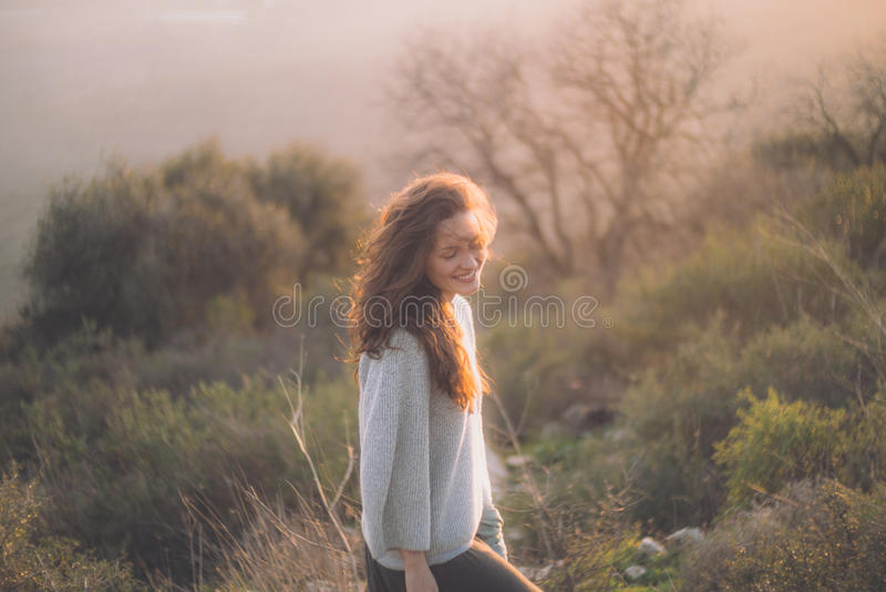 Belle jeune fille souriant au coucher du soleil photographie stock libre de droits