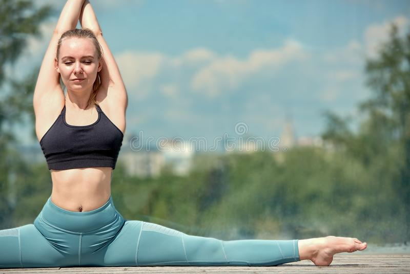 Belle jeune fille sportive dans les vêtements de sport, faisant des exercices pour s'étirer sur la rue, l'élément de la gymnastiq photographie stock libre de droits