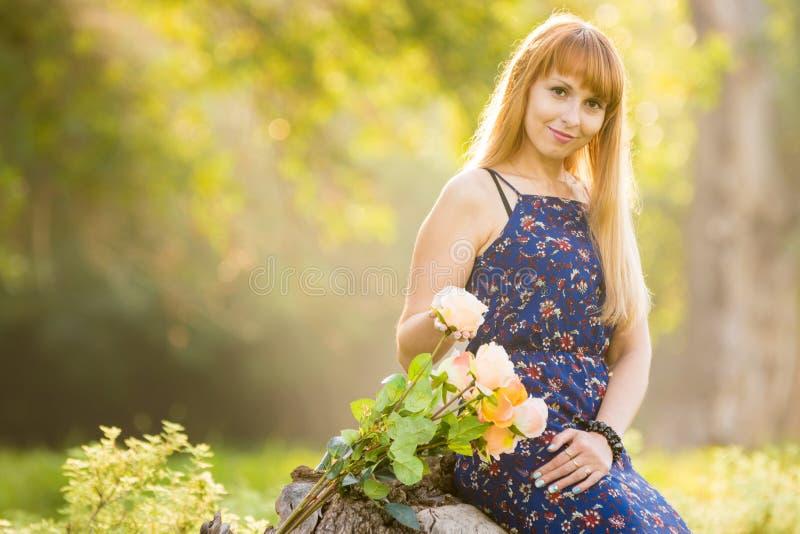 Belle jeune fille sur le fond de la verdure brouillée ensoleillée, mensonges à côté d'un bouquet des roses photographie stock