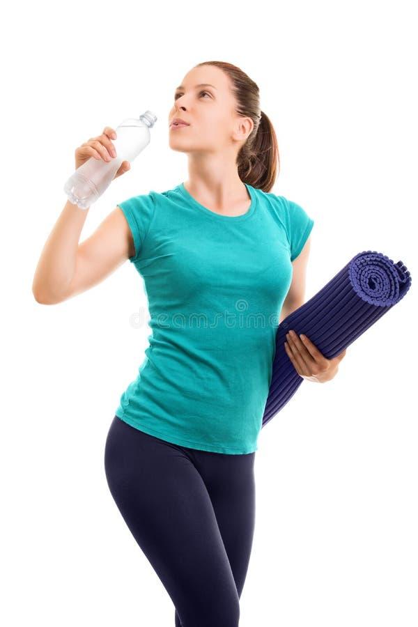 Belle jeune fille tenant le tapis d'exercice, eau potable  photographie stock libre de droits