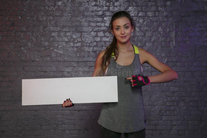 Belle jeune fille tenant un conseil vide, l'espace de copie pour annoncer, les muscles et le gymnase, photo conceptuelle, espace  photos stock